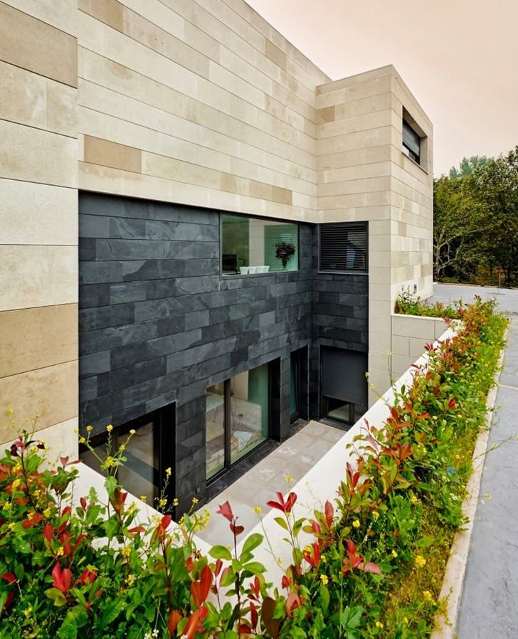 Black and brown stone facade on Modern home by Foraster Arquitectos