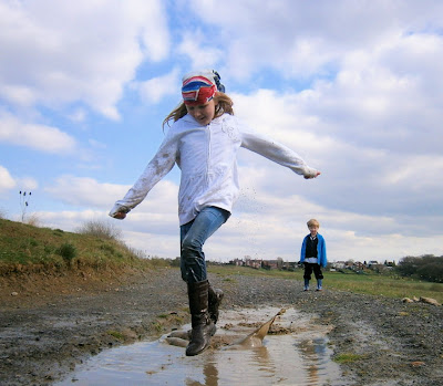 girl jumping in muddy puddle wearing next olympic supporters scarf style for london 2012