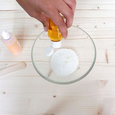 Una mano vaciando esencia en la sal de un bol