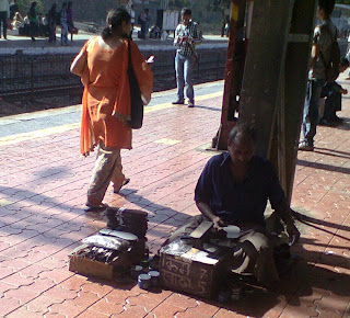 Shoe shine man polishing shoes at railway station, andheri bandra cst central railway