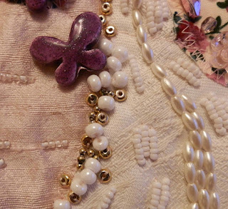 Close up of Pink bead embroidery showing purple ceramic butterfly bead, oval pearls and small gold and white beads