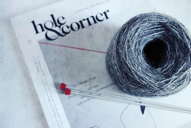 Image of knitting yarn and needles left on top of a magazine.