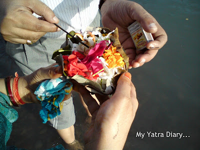 Leaf Diya (candle) being ignited to be floated on the Ganges