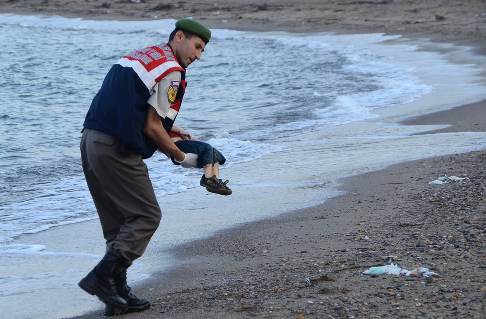 70 Of The Most Touching Photos Taken In 2015 - A Turkish police officer carries the lifeless body of a Syrian child after a boat carrying refugees sank trying to reach the Greek island of Kos.