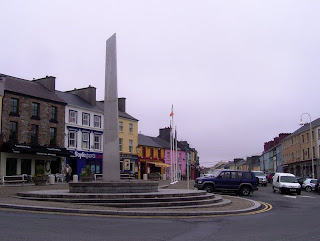 Obllisque statue in the middle of  a roundabout-cum-market-square in the middle of Clifden village, outside the Derryclare and EJ Kings pubs.