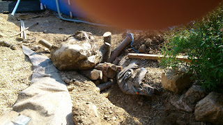 Using levers and 40 pieces of wood as props underneath we managed to inch the big stone out of the hole