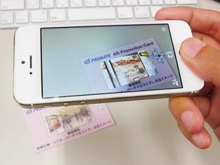名刺の裏をスマートフォンをかざして映像が流れる写真