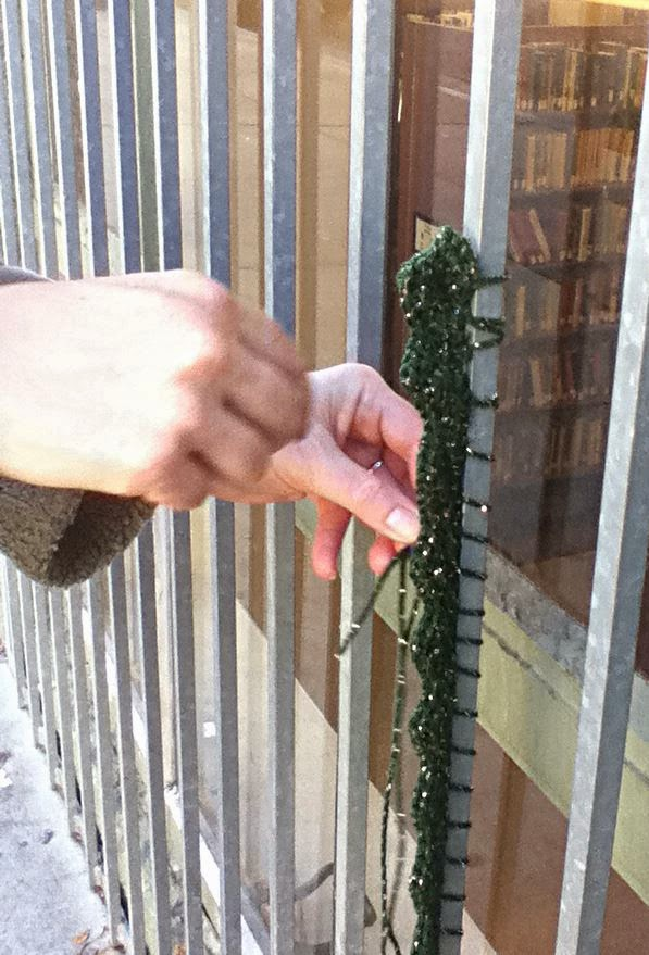 Hands attaching length of crocheted scallop edging to metal bar over window. Through the glass of the window, library shelves with books are visible.