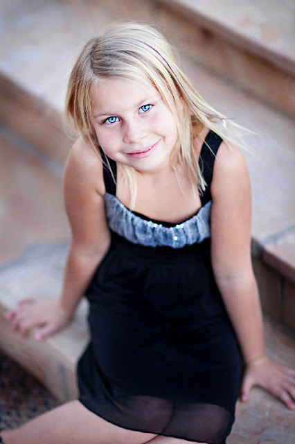 Beautiful girl smiles up at camera of family photographer