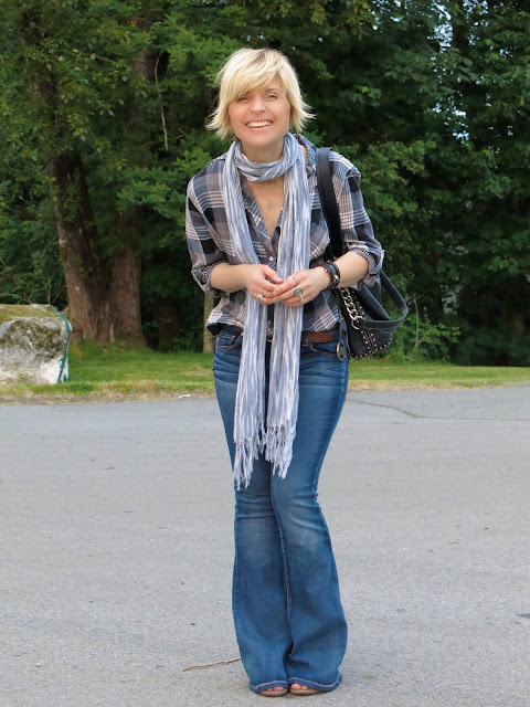 styling flare jeans with an oversized plaid shirt and a striped scarf