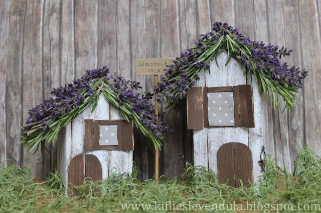 Dos casitas de cajas de cartón pintadas y con un tejado de ramitas de romero.