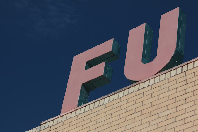 A large F U sign on a brick building  in front of a deep blue sky.