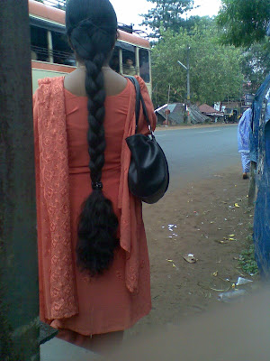 South Indian long hair college girl with long braid waiting at bus stand.