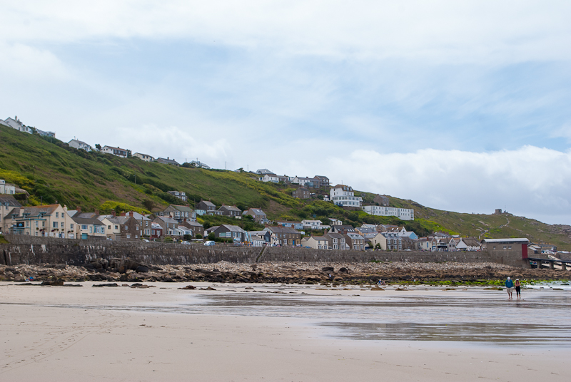 View of green fields and houses from the sennen cove beach
