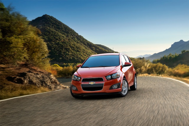 Orange 2013 Chevrolet Sonic LTZ Turbo on winding road