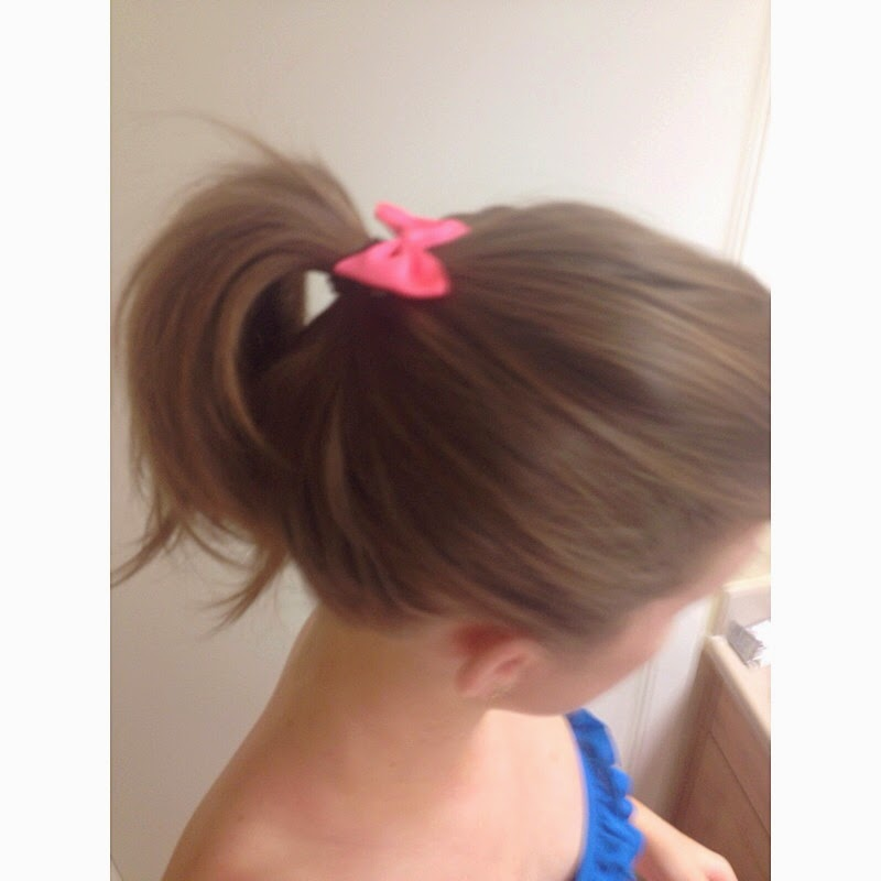 Royal blue ruffle swim suit with pink hair bow and pony tail