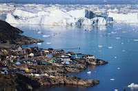 The village of Ilulissat is seen near the icebergs that broke off from the Jakobshavn Glacier on July 24, 2013 in Ilulissat, Greenland. Significantly greater sea level rise will occur with the melting of the West Antarctic and Greenland ice sheets, giant masses of ice that are vulnerable to even a slight increase in temperature, a new study finds. (Credit: Joe Raedle/Getty Images) Click to Enlarge.