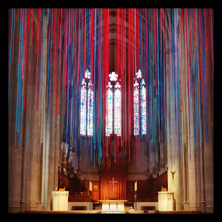 Thousands of different-coloured lengths of ribbon, hanging from the ceiling, facing the altar