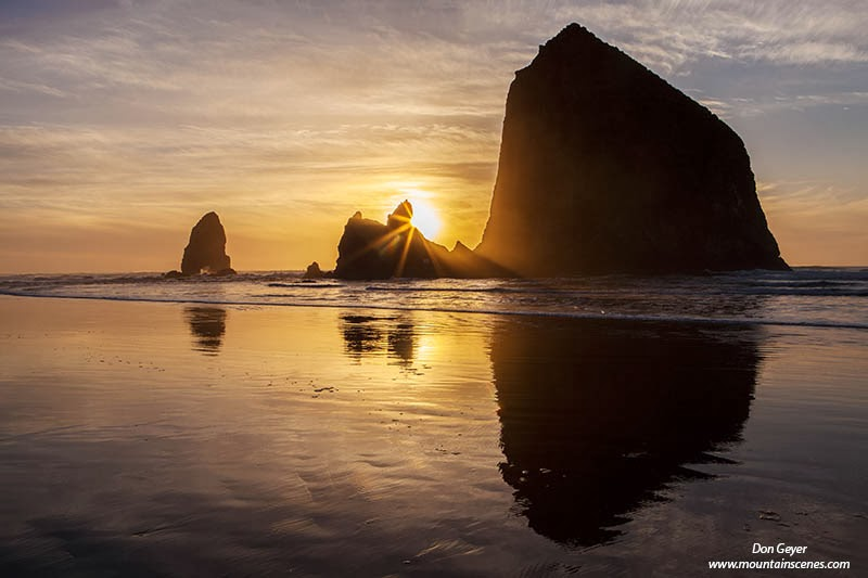 The sun sets behind Haystack Rock at Cannon Beach, Oregon.