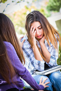 A distraught woman on a college campus is comforted by a friend.