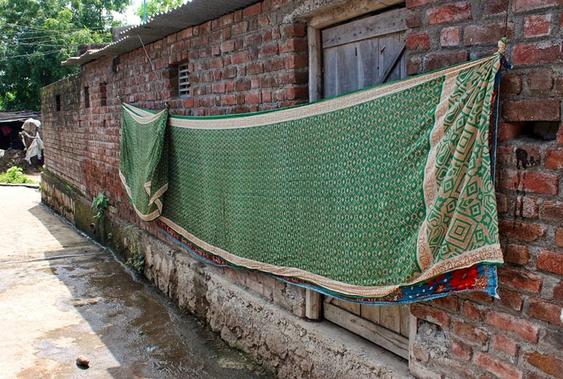 sari being hung out to dry on a village wall
