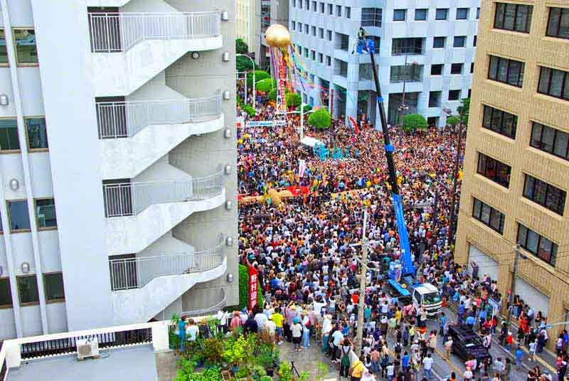 gold ball,streamers,crane,crowd,street