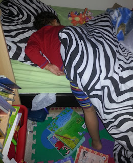 Toddler hanging out of bed still asleep
