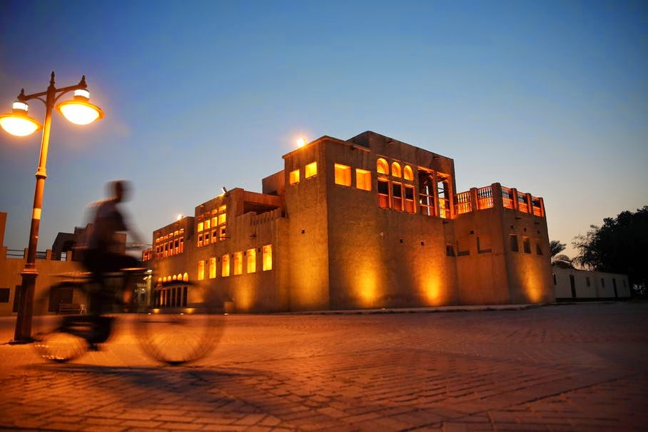 In this Tuesday, June 3, 2014 photo, a man rides his bicycle past the Sheik Mohammed bin Rashid Al Maktoum House, a historic building by the creek, in Dubai, United Arab Emirates. The city is awaiting the results of a bid for Dubai Creek to be declared a UNESCO World Heritage Site, and a $544 million creek-side project has been approved by Sheik Mohammed bin Rashid Al Maktoum, UAE vice president and prime minister and ruler of Dubai, that aims to transform the area into a cultural and artistic hub for the city.
