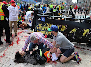Sydney Corcoran, 18, is tended to at the finish line of the Boston Marathon, .