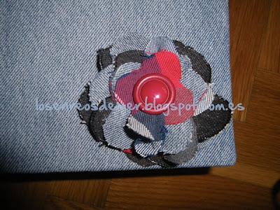 Flor realizada con tela vaquera, con tela de cuadros y un botón
