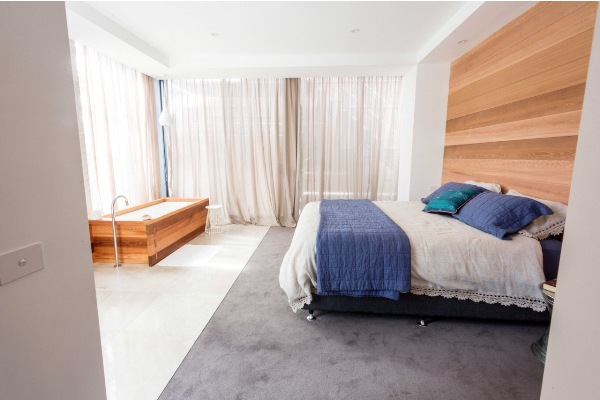 Luxury A large walk in wardrobe with hidden storage behind the mirror will satisfy any couple occupying this space while the floor tiles extend from the bath area