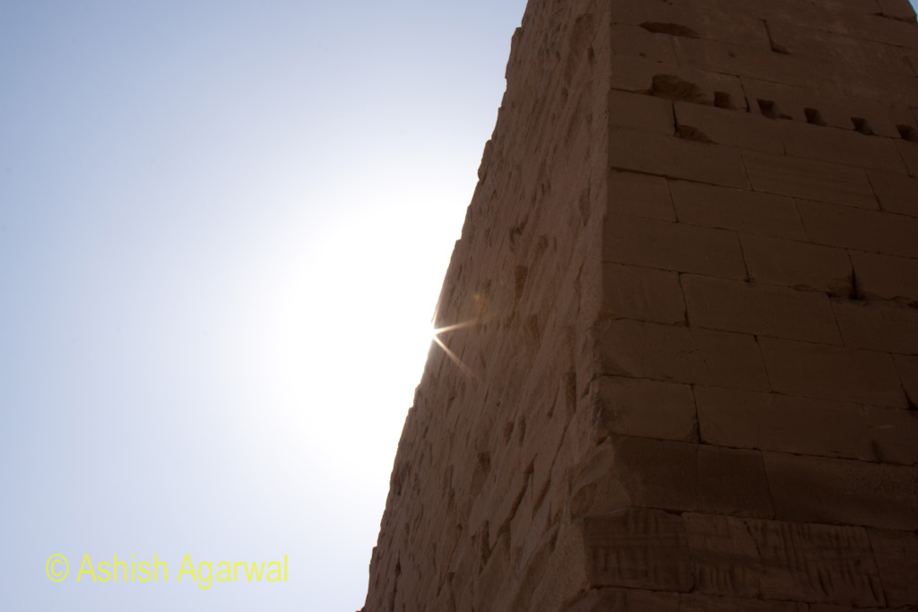Sun emerging from behind a structure of the Karnak temple in Luxor