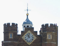 Twin brick towers with a clock in the centre on a diamond-shaped background