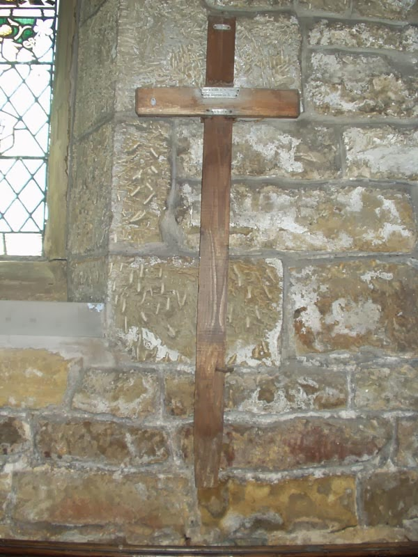 A wooden cross, about three feet tall, hanging on a stone wall.  The cross has metal labels on it near the intersecion of the two piece of wood.