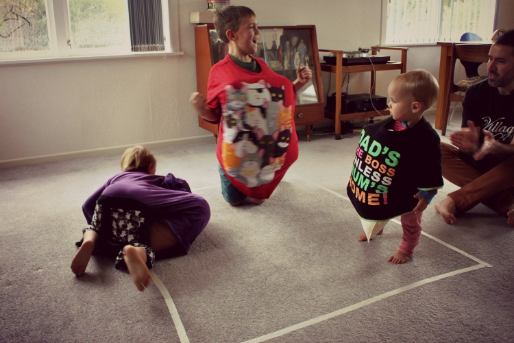 Two boys sumo wrestling and a baby watching