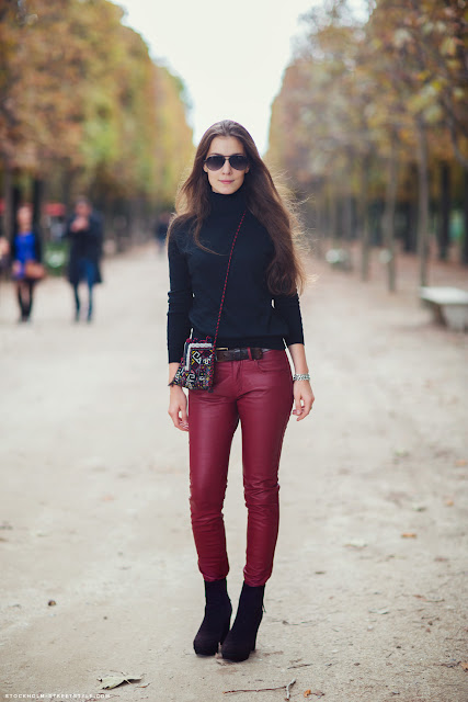 Streetstyle woman wearing black shirt with red leather pants and black booties.