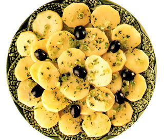 Salad of sliced potatoes garnished with a vinaigrette dressing, green onions and black olives