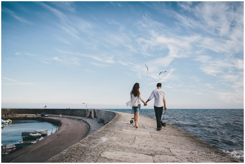 Engaged couple walking along cob by sea front
