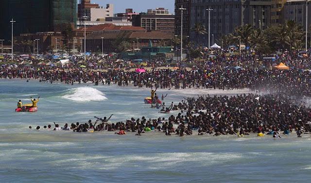 """Спасатели """"рулят"""" толпой во время празднования Нового года на пляже в городе Дурбан, ЮАР. Местные жители традиционно погрузились в воду на Новый года"""