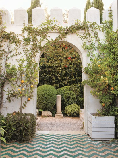 ourtyard with turquoise Moroccan tiles in a chevron pattern, white archway and fruit trees