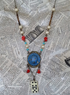 eclectic necklace with blue, red, pearl, and antiqued brass