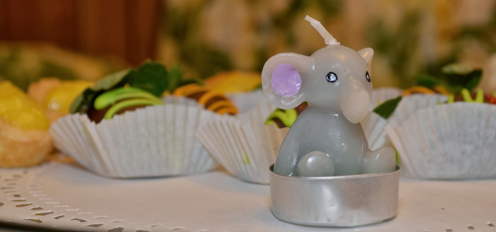 Baby elephant candle on tray of chocolate dipped strawberries and lemon tarts