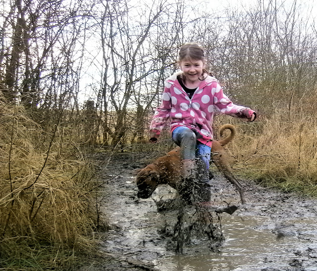 girl splashing in puddle mud water dirt