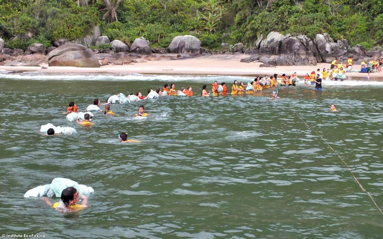 "Calouros e veteranos formaram uma ""corrente ecológica"" para transportar o lixo da praia para a escuna. Crédito: Instituto EcoFaxina"