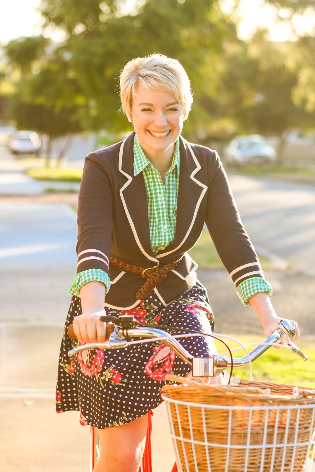 Liana of Finding Femme wears Modcloth Academia Ahoy blazer in navy, C Wonder green gingham shirt, Modcloth navy polka dot and floral a-line skirt with red Reid Cycle bike.