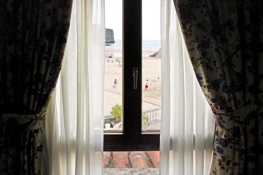 Pormenor da praia vista através duma nesga de cortina de janela