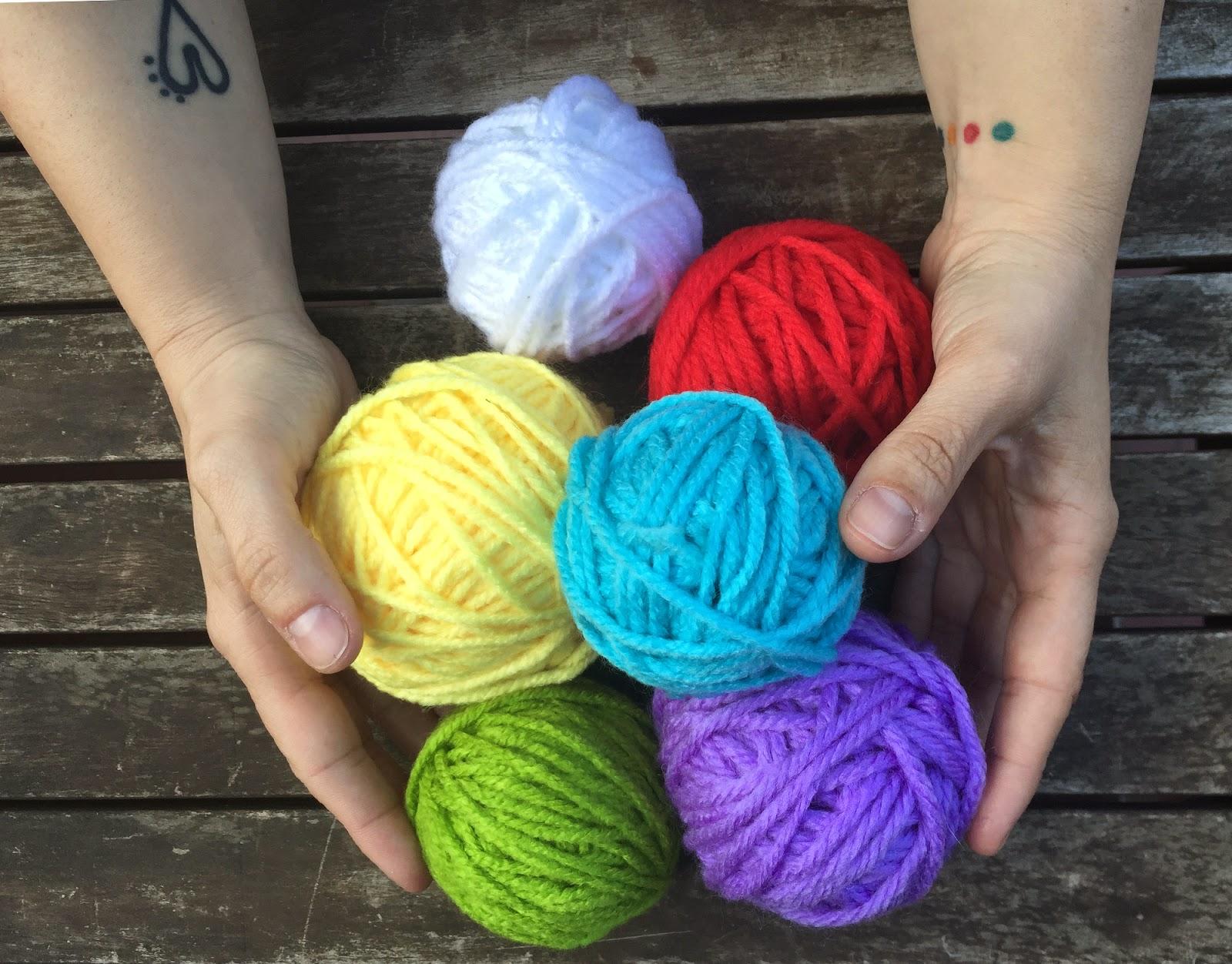 ovillos-de-lana-de-colores-hechos-a-mano-y-sujetos-con-las-manos-de-Clara-Montagut