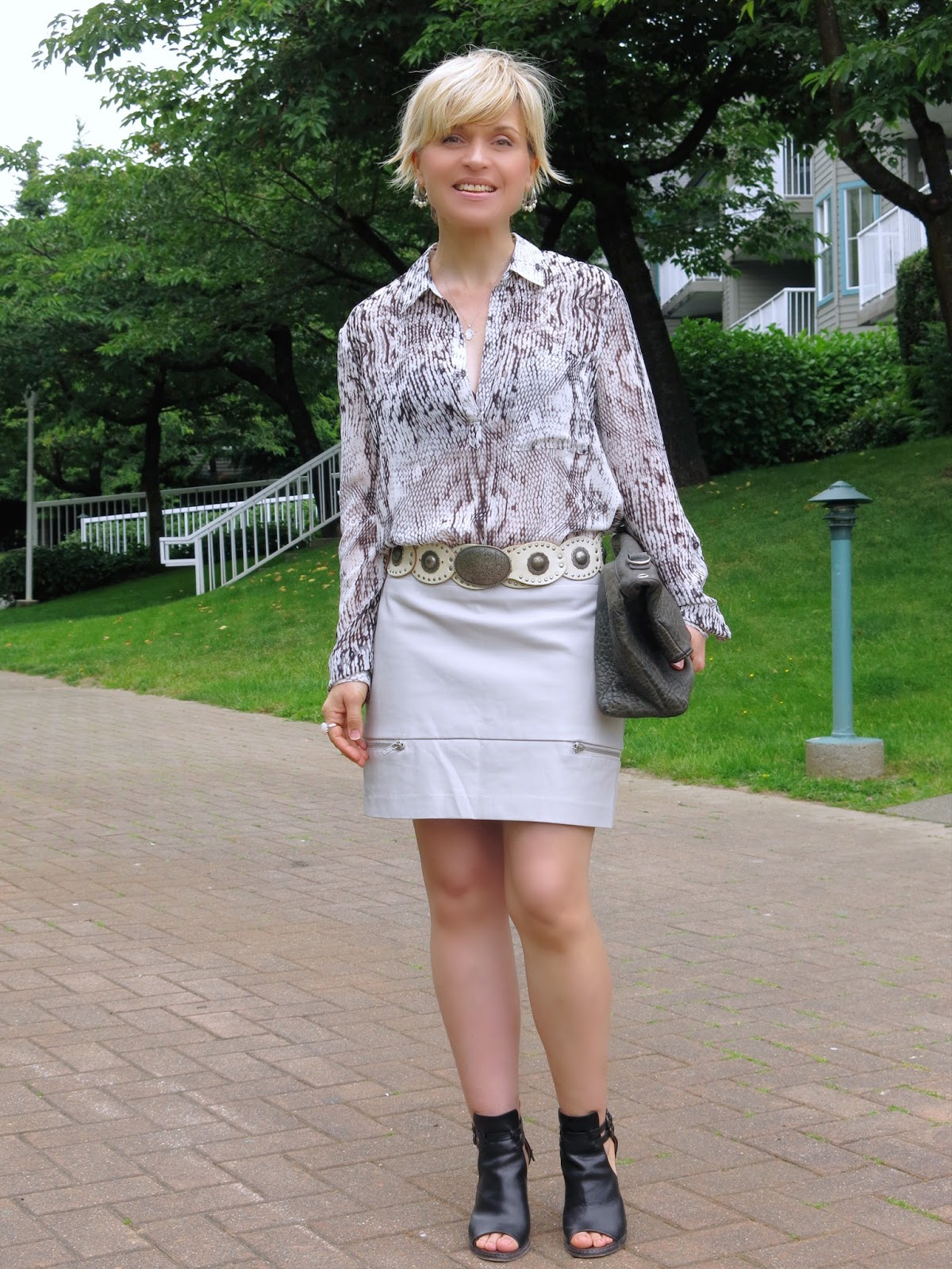 styling a faux-leather miniskirt with a snake-print blouse and concho belt