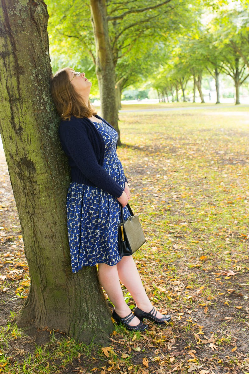 A large woman in a park in a 1950s-style Boden dress