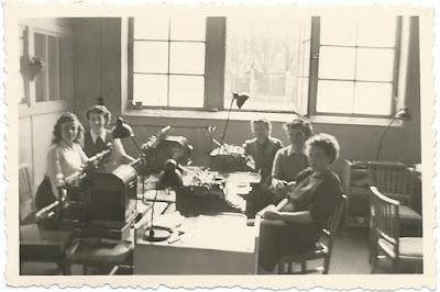 S/W-Foto aus den 1930-er (?) Jahren des letzten Jahrhunderts, rund um einen Schreibtisch mit vielen Schreibmaschinen darauf sitzen Damen und lächeln in die Kamera.
